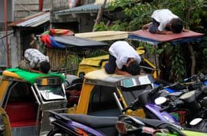 Muslim youths pray atop auto-rickshaws in front of al-Satie mosque in Baseco, Manila