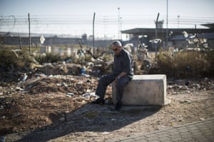 A Palestinian Muslim waits for a bus near Ramallah, West Bank