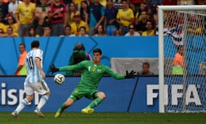 Thibaut Courtois makes himself big to block Messi's shot.