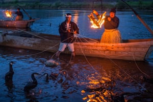 Cormorant masters and boatmen prepare the sea cormorants by tying snares around their necks, preventing them from swallowing fish they catch.