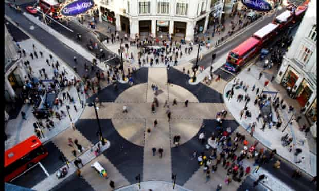 Pedestrians cross the new diagonal road crossing at Oxford Circus in London. The design of the new pedestrian crossing was inspired by the Shibuya crossing in Tokyo and allows pedestrians to cross diagonally.