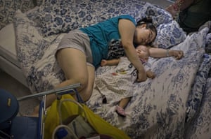 A shopper sleeps with her child on a bed in the showroom.