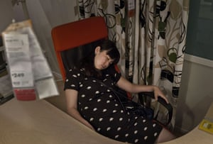 A shopper sleeps in an office chair.