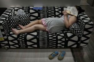 A shopper sleeps on a sofa in the showroom.