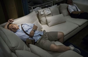 Shoppers sleep on a sofa in the showroom.