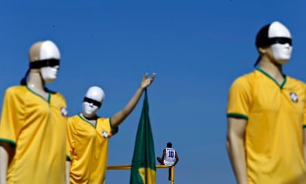 A man sits on top of a goal post next to mannequins that are part of a anti-Fifa demonstration,