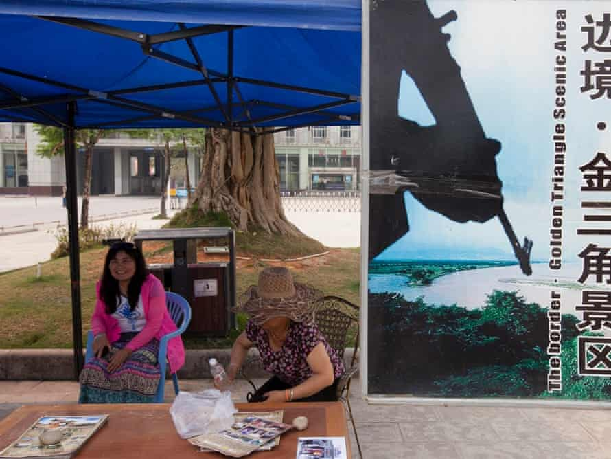 Two young women run a booth for tourists next to the Chinese border with Burma advertising tours to the 'Golden Triangle Scenic Area', in Daluo, the border town with Burma, Xishuangbanna, Yunnan Province, China.