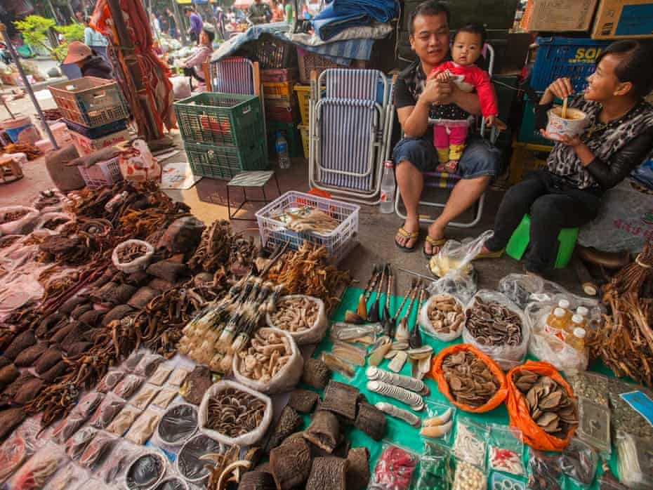 A trader of illegal wildlife products is seen with his family at a covered market in the town of MongLa, Shan State Special Region Four, Burma