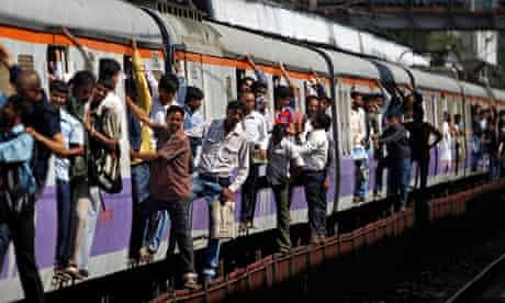 Commuters hang outside a train in Mumbai