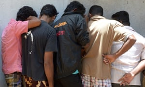 Sri Lankan asylum seekers sent back by Australia cover their faces as they wait to enter a court in the southern port district of Galle.