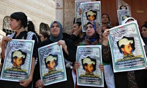 Women from Mohammed Abu Khdeir's family hold pictures of the killed Palestinian teenager