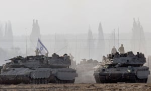 Israeli soldiers stand on Merkava tanks in an army deployment area near Israel's border with the Gaza Strip. Israeli warplanes pounded Gaza with more than 50 strikes overnight after Hamas militants fired scores of rockets over the border, dragging the two sides towards a major conflict.