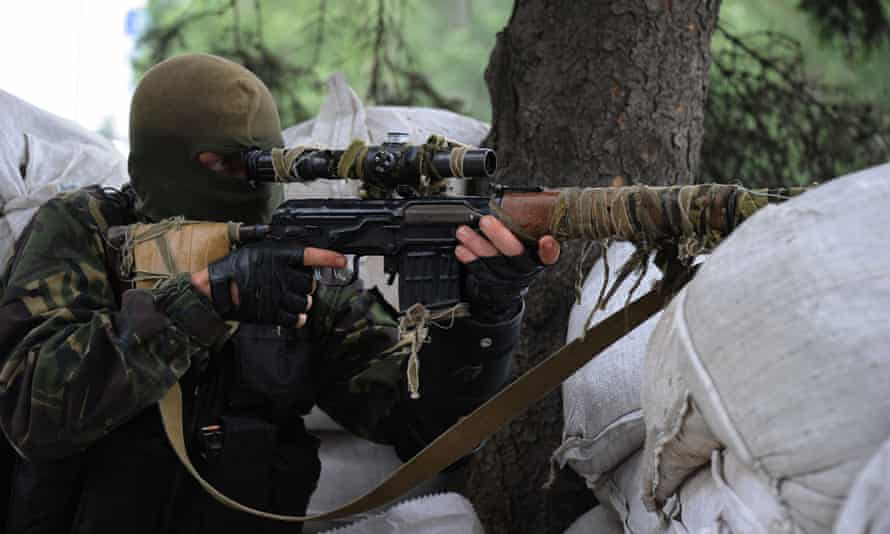 Pro-Russian militant of the Vostok batallion looks through the scope of his rifle as he guards a checkpoint on 8 July, 2014 in Donetsk, eastern Ukraine.