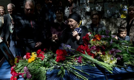 The mother of Dmitriy Nikityuk, a Cossack, holds a candle next to his coffin during his funeral in Odessa, Ukraine, on 8 May, 2014. Nikityuk died in the burning trade union building fire that killed most of the 40 people that died after riots erupted.(AP Photo/Vadim Ghirda)