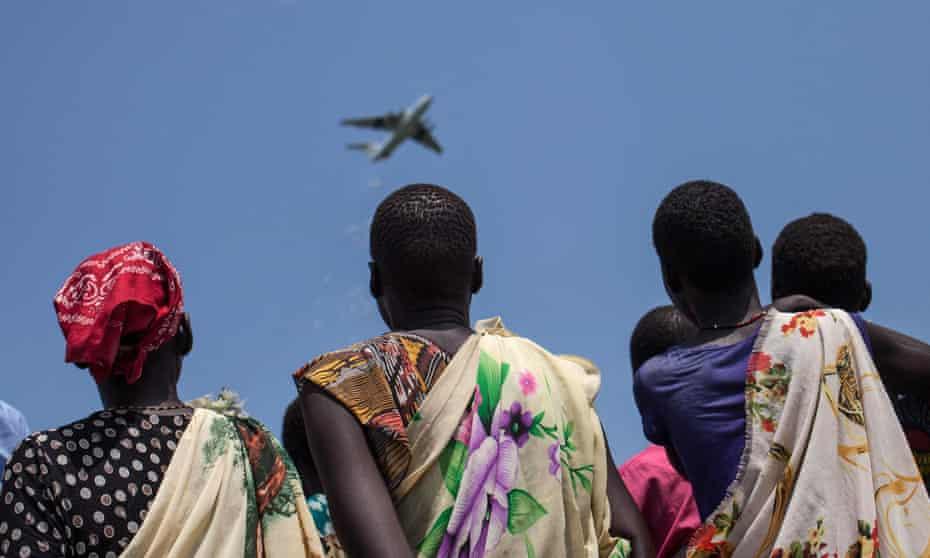 Women look at an International Red Cross dropping emergency food supplies in Leer, South Sudan, on July 5, 2014.