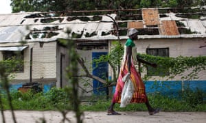 A woman walks on July 7, 2014 past one of the buildings of the Leer Hospital that was burned during the fighting.