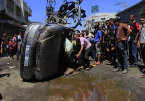 Gaza, Palestinian Territory. 8th July 2014 -- Palestinians inspect a destroyed car following an Israeli air strike in central Gaza.