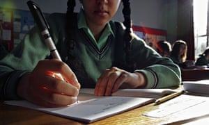 A girl works at a desk during a school lesson