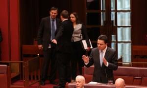 Independent senator Nick Xenophon speaks as Ricky Muir consults his preference whisperer Glenn Druery.