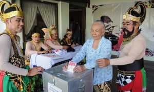 """Indonesian election officials wearing Javanese """"wayang"""" costumes assist voters in Solo in central Java island on July 9, 2014. (AFP PHOTO / ANWAR MUSTAFAANWAR MUSTAFA/AFP/Getty Images)"""