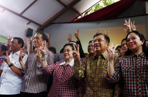 Indonesian Presidential candidate Joko Widodo (second left) and his running mate Jusuf Kalla (second right), with supporters, raise victory fingers as they celebrate their lead on the quick count.