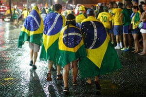 Mourning Brazil: Brazil football fans walk in the rain