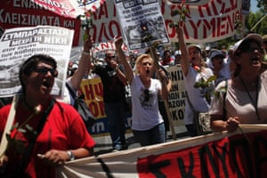 Greek state workers hold banners and roses as they shout slogans during a rally in Athens July 9, 2014.