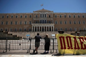 Tourists look at the Greek parliament as state workers hold a banner during a rally in Athens July 9, 2014.