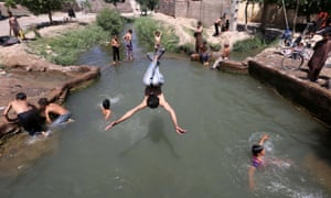 Afghan children cool off at a pond to escape the heat on a hot day in Herat