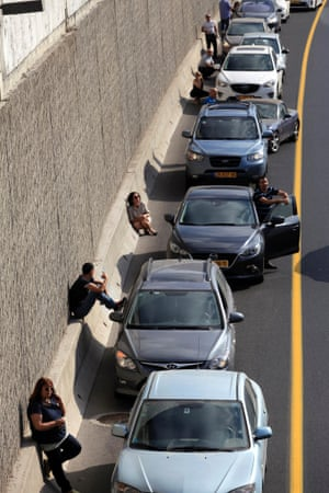 Drivers take cover beside their cars on a highway as an air raid siren, warning of incoming rockets, sounds in Tel Aviv