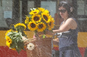 A woman with sunflowers in a basket rides her bike behind a water sprinkler in Warsaw, Poland with mercury set to rise to 33 C / 91 F