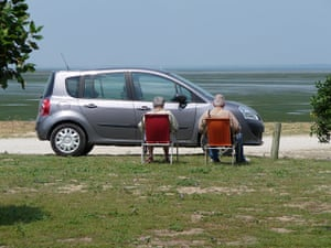 Your Pictures: Sunbathe: Two people sitting in the sun infront of a car