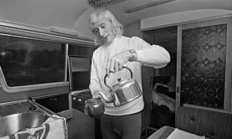 English DJ and television presenter Jimmy Savile making himself a pot of tea in his motor home, 31 D