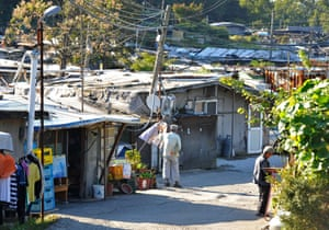 Elderly residents stand outside their homes in Guryong.