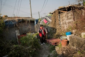 Luo In-soon walks to her Guryong Village home.