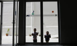 Children play by a window inside a Catholic migrant shelter in San Luis Potosi
