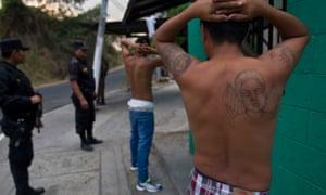 Members of the Salvadoran national police detain two men during an anti-gang raid in San Salvador.