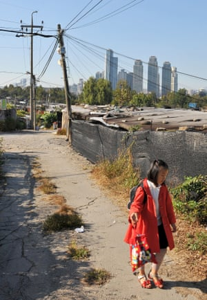 A school girl walks along a road lined with a shacks. The illegal encampment grew up on private land in 1988.