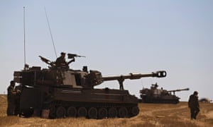 An Israeli soldier sits atop a mobile artillery unit stationed near the border with the Gaza Strip