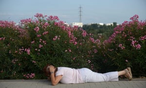 An Israeli woman covers her head and lays on the ground while sirens sound in the southern city of Ashdod.