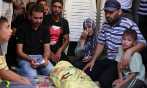 A father and mother cry the death of their young child, one of the seven members of Kawareaa family dead following an Israeli airstrike, in the town of Khan Younis. palestine gaza funeral israel