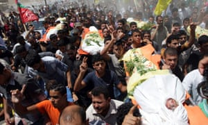 Relatives and friends carry the bodies of the al-Kaware family as they mourn during their funeral. gaza palestine