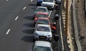 Israelis take cover near their cars on the central highway while sirens sound over Tel Aviv.