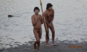 Two members of a previously uncontacted tribe stand on the bank of the Envira river.