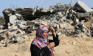 A Palestinian woman reacts upon seeing her destroyed home after it was hit by Israeli shelling in Gaza.