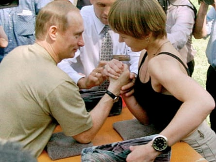 At a festival in central Russia, Putin defeated a young woman at arm-wrestling and retrieved a coin from a tub of fermented milk with his teeth.