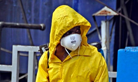 An employee of the Monrovia City Corporation sprays disinfectant on a street.
