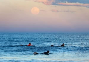 The super moon looms over surfers in Sydney, Australia/.