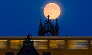 The supermoon rises behind Oberbaum Bridge as a train passes through in Berlin, Germany.