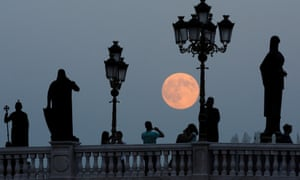 People take photos as a perigee moon also known as a supermoon rises above a bridge over Vardar River in Skopje, Macedonia.